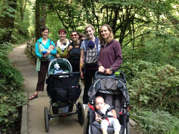 5 women, 5 babies and 2 strollers on a lush green nature path