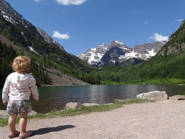 Little Girl standing in front of a mountain lake with the Maroon Bells in the background