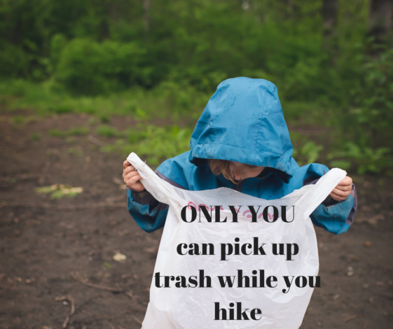 "Child holding a garbage bag on a hike with the words ""Only you can pick up trash while you hike"""