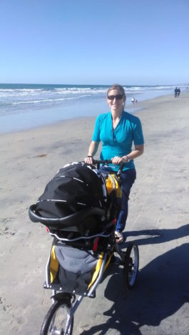 woman on beach with a joggine stroller using the infant car seat adapter