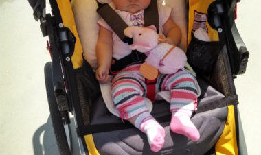 Young infant in jogging stroller with head support cushion