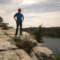 Man standing on rock overlooking lake