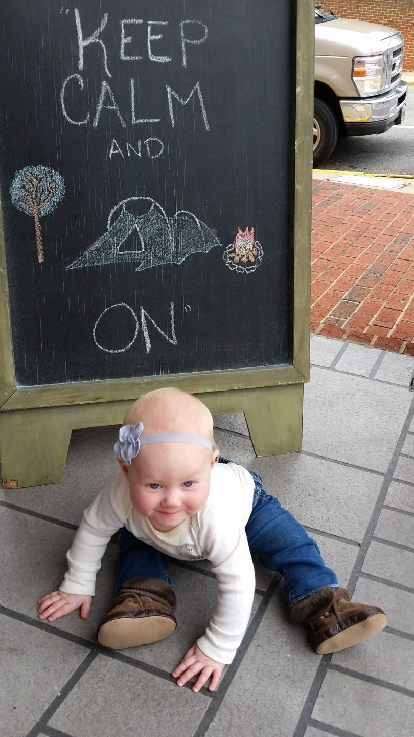 "Infant in front of a ""Keep Calm and Camp On"" Sign."