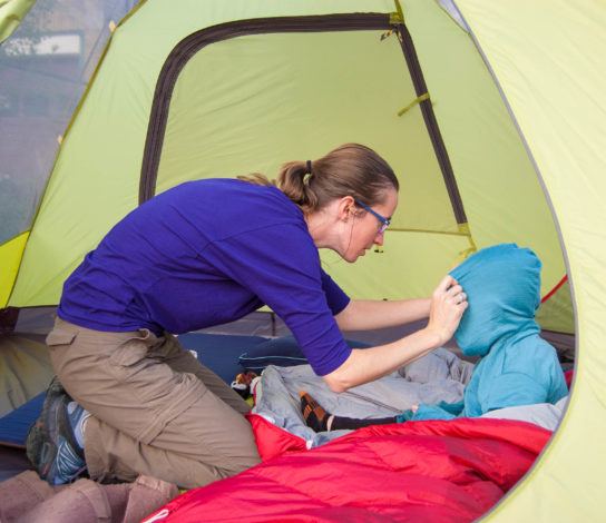 Mom adjusting the hood on a kid's hoodie while they sit in a tent