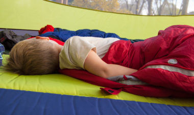 young boy sleeping in a tent with a red sleeping bag and a wool t-shirt