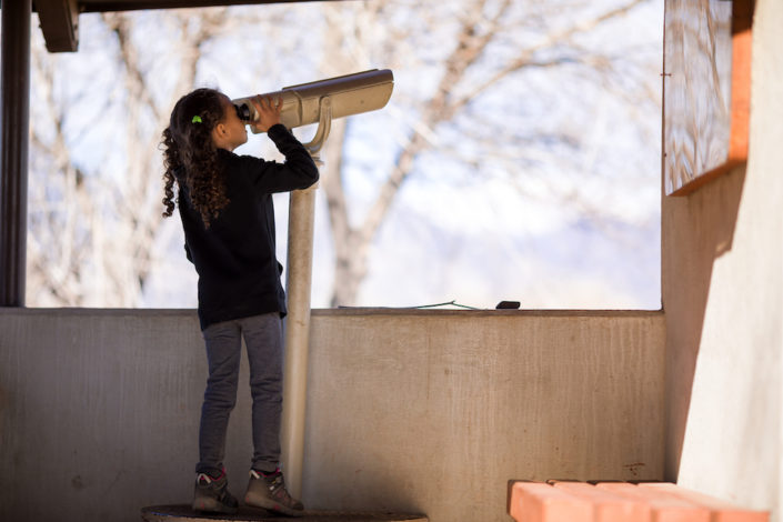 Girl looking through telescope at a park