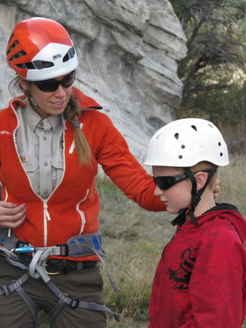 Park ranger Roberta teaches a young student how to climb.