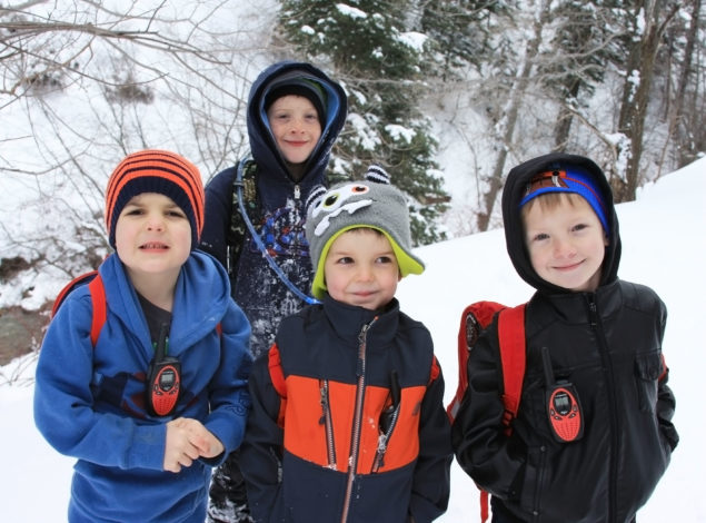 4 boys on a winter trail with hiking backpacks