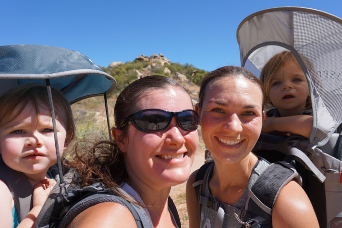 Hiking with a Hearing Loss by Vanessa Wright for Hike it Baby (image two moms with their daughters in hiking frame carriers, smiling at the camera)