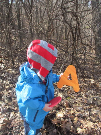 A is or Alphabet Themed Hikes by Moriah Butler for Hike it Baby (image of small child in a blue rain suit holding a foam letter A)