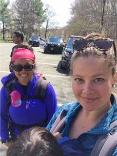 Two women hikers with kids in carriers in a parking lot with emergency vehicles in the background