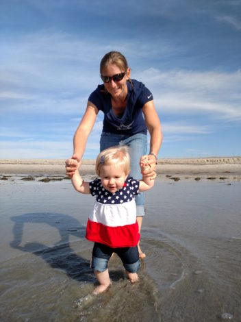 Simple, Quick and Easy Outdoor Activities for Infants by Kirby Crawford for Hike it Baby (image of a mom and her baby girl practicing walking along a beach)