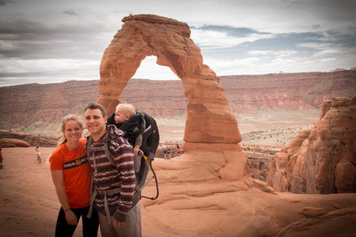 Couple with a child in a frame carrier standing in the desert of Moab