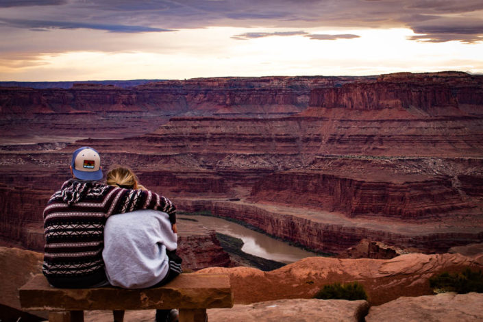 Couple on a bench in Moab desert overlooking a canyon