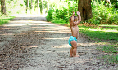 Cloth Diapering while Hiking by Andrea Zimmer for Hike it Baby (photo by Lauren Adams: image o a child wearing a blue cloth diaper walking barefoot down a trail)