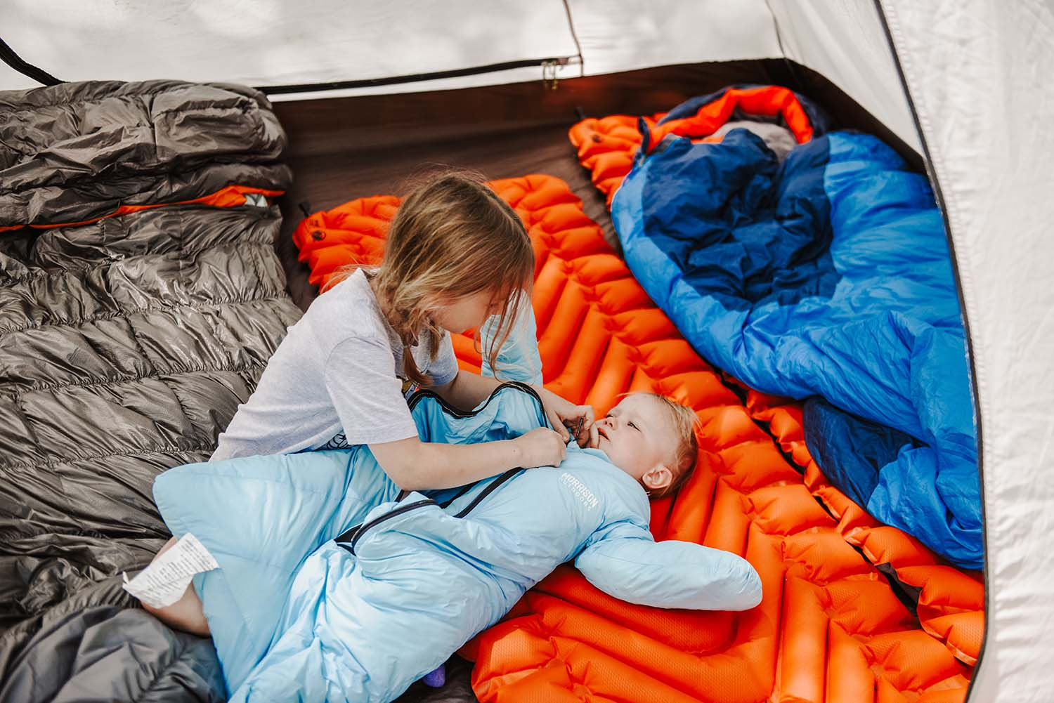baby and young child in tent wtih sleeping bags