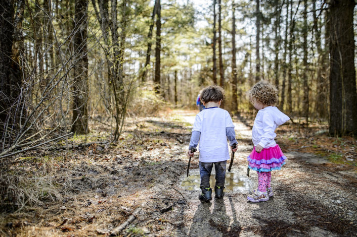 a young boy and girl hiking on a wooded trail