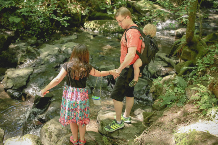man with a child on his back in a carrier and a young girl stand by a rocky streambed