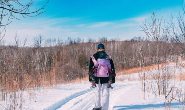 Man snowshoeing down a trail wearing a toddler on his back
