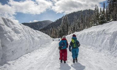 two kids hiking on a snowy trail