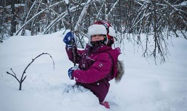 girl child sitting in the snow smiling