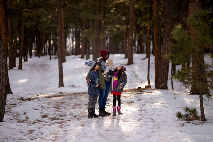 mom and kids in the snowy woods together