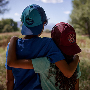 trail friends - two kids in trucker hats looking out at a field