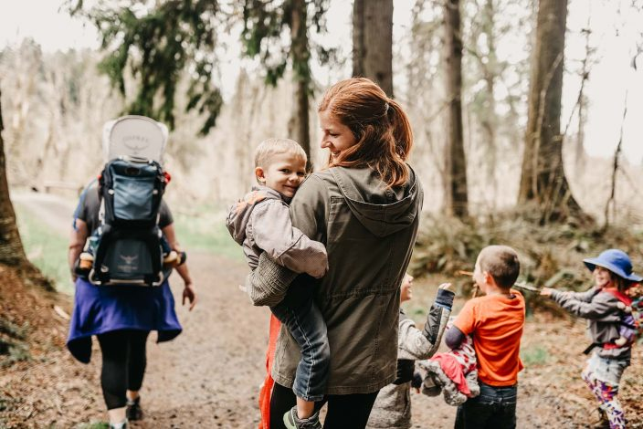 mom with baby and other moms and kids on a nature walk hike