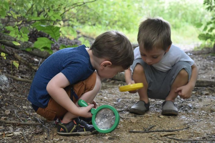 boys looking at nature with magnifying lenses