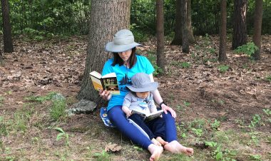 Mom and baby outside reading