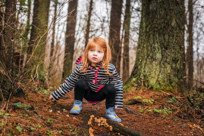 young girl in the woods wearing rain gear