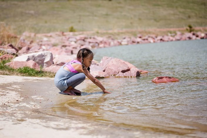 young girl playing on the sie of a lake