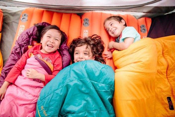 three young children in sleeping bags camping