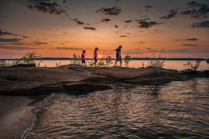 three boys hiking at sunset along the beach