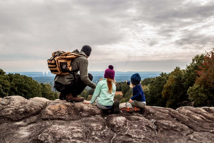 dad with two kids hiking with a mountain view