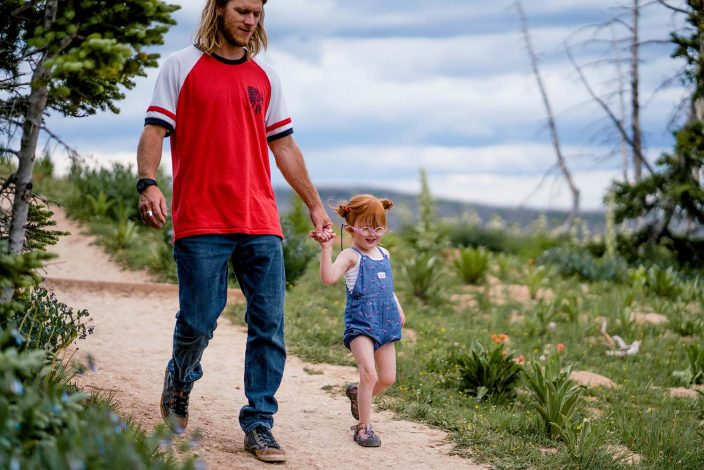 dad walking with young daughter on a hiking trail