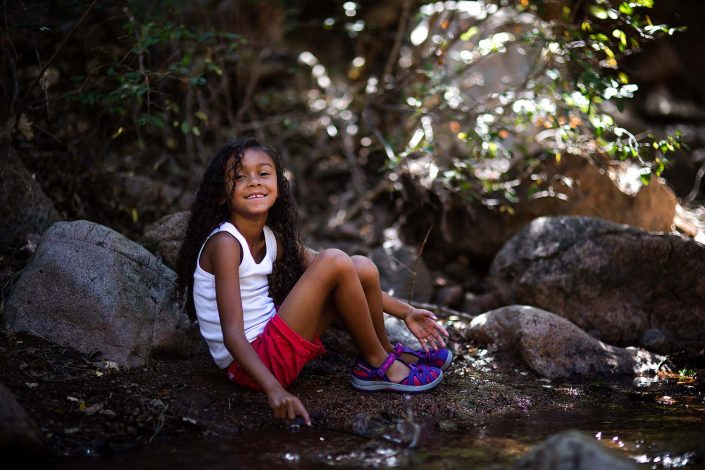 girl sitting by side of the creek