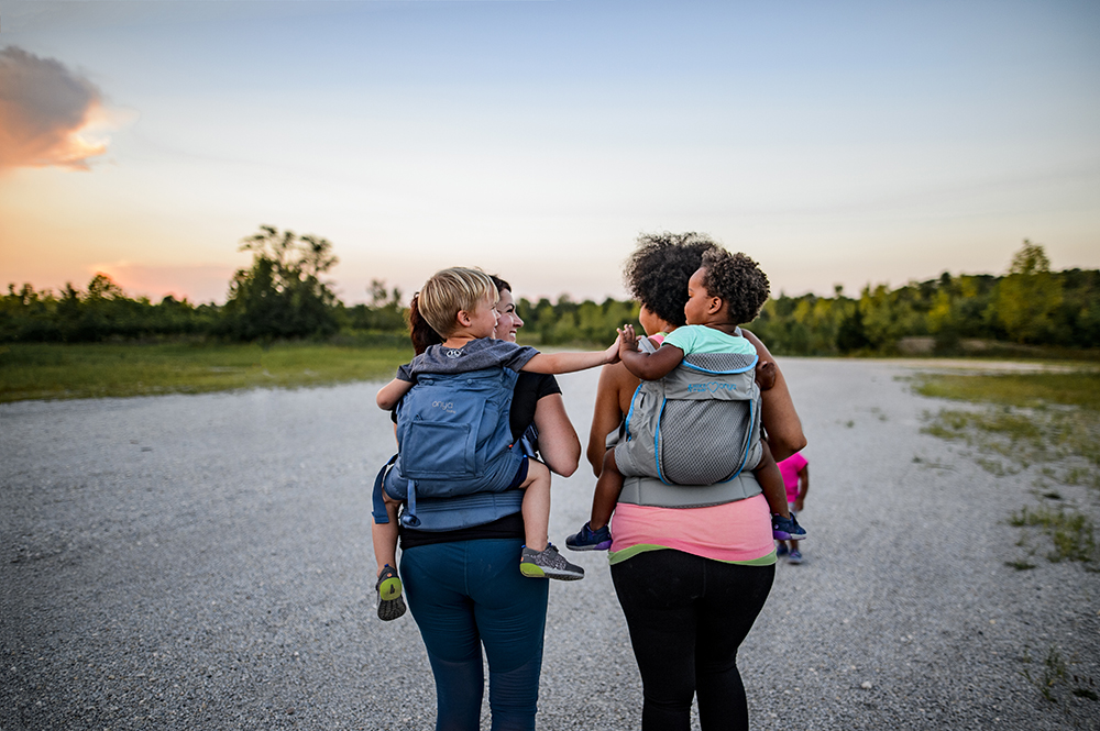 White woman carrying a young boy in a baby carrier on her back, walking with a black woman carrying a young black baby on her back. The two children are holding hands.