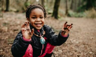 young girl smiling while playing in the mud