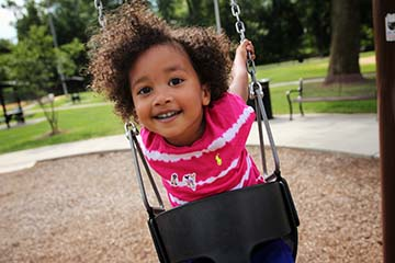 young black girl playing on a swingset