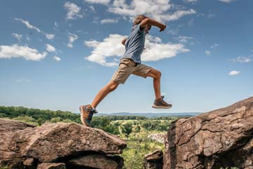 young boy jumping between two rocks