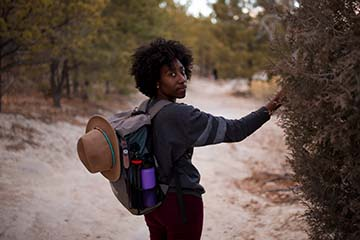 black woman on a dirt hiking trail turning to face the camera