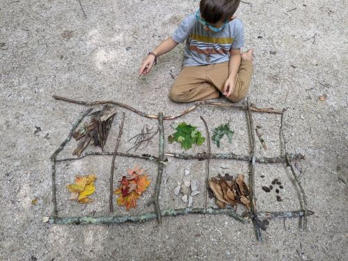 Child using nature for math activity.