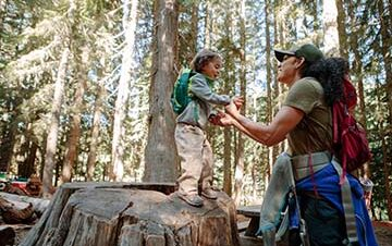 mom helping toddler walk on large tree stump