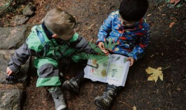 boys reading a book outside