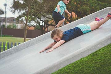 young girl sliding face first down playground slide