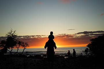 man holding boy on shoulders looking at sunset