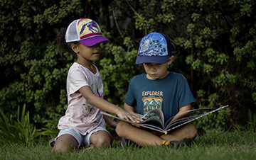 Young girl and boy reading a book outside.
