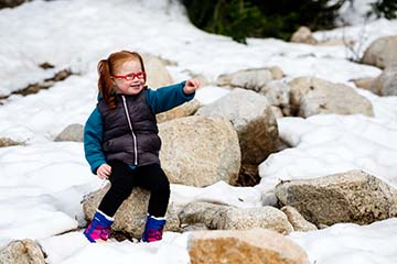 girl sitting on rocks in the snow