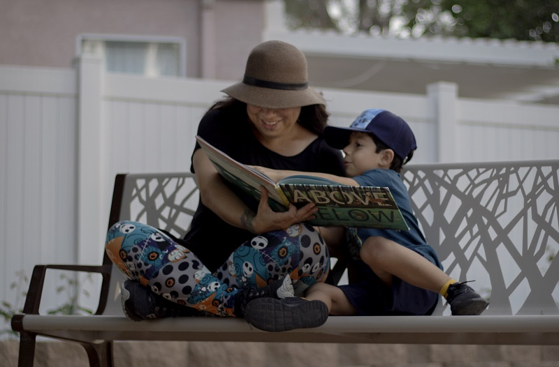 mother and son sitting on a park bench reading a book